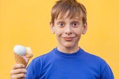 Der Junge mit Eiscreme auf gelbem Hintergrund Stockfotos
