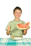 Der Junge mit Melone am Tisch Lizenzfreie Stockbilder