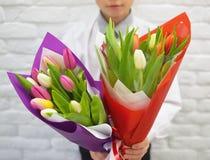 Der Junge mit schönen Blumensträußen von Tulpen lizenzfreie stockbilder