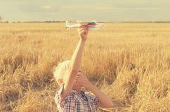 Der Junge mit seiner Hand lässt das Modell der Fläche in den Himmel laufen Stockfotos