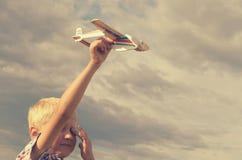 Der Junge mit seiner Hand lässt das Modell der Fläche in den Himmel laufen Lizenzfreies Stockfoto