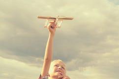 Der Junge mit seiner Hand lässt das Modell der Fläche in den Himmel laufen Lizenzfreies Stockbild