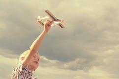 Der Junge mit seiner Hand lässt das Modell der Fläche in den Himmel laufen Stockfoto