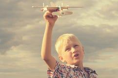 Der Junge mit seiner Hand lässt das Modell der Fläche in den Himmel laufen Stockbild