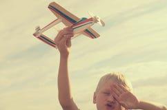 Der Junge mit seiner Hand lässt das Modell der Fläche in den Himmel laufen Lizenzfreie Stockfotos