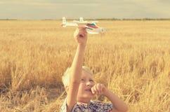 Der Junge mit seiner Hand lässt das Modell der Fläche in den Himmel laufen Lizenzfreie Stockbilder