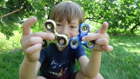 Der Junge, der mit der Spinner-Druckentlastung mit zwei Unruhen spielt, spielt im Freien stock footage