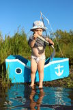 Der Junge mit zwei Jährigen überprüft ein Teleskop auf dem Ufer Lizenzfreies Stockbild