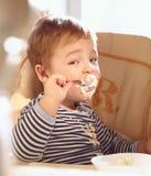 Der Junge mit zwei Jährigen isst Brei morgens. Stockfotografie