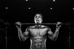 Der junge muskulöse Mann, der Zug tut, ups auf Stange Stockbilder