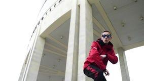 Der junge nette lustige Kerl, der rote Jacke und Sonnenbrille trägt, singt an der Winterstraße stock video footage