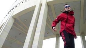 Der junge nette Mann, der rote Jacke und Sonnenbrille trägt, singt an der Winterstraße stock footage
