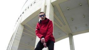 Der junge nette Mann, der in der roten Jacke und in der Sonnenbrille gekleidet wird, singt an der Winterstraße stock video