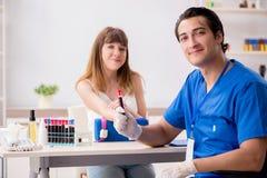 Der junge Patient während des Blutprobe-Stichprobenverfahrens stockfoto