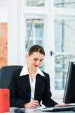Rechtsanwalt im Büro, das Anmerkungen in einer Datei macht Stockfotos