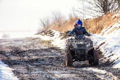 Der Junge reitet ein ATV nicht für den Straßenverkehr lizenzfreie stockfotografie