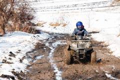 Der Junge reitet ein ATV nicht für den Straßenverkehr stockfotos