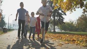 Der Junge reitet einen Roller im Herbstpark Freunde holen einen Jungen ein, der draußen einen Roller reitet Kinder mit Vorstand stock video footage