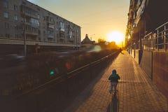 Der Junge reitet einen Roller in Richtung zur Bewegung stockbild