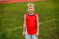 Der Junge in der roten Weste, die auf grünem Gras steht lizenzfreies stockfoto
