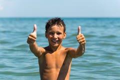 Der junge schöne Junge, der den hohen Daumen zeigt, unterzeichnen herein das Meer Lizenzfreies Stockbild
