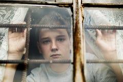 Der Junge schaut aus dem Fenster heraus durch ein Gitter lizenzfreies stockbild