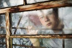 Der Junge schaut aus dem Fenster heraus durch ein Gitter lizenzfreie stockfotografie