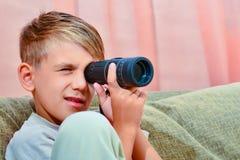 Der Junge schaut in einem Monokel stockfotos