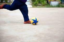 Der Junge schießt einen Fußball Stockfotos