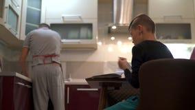 Der Junge schlägt durch die Seiten eines Buches mit kulinarischen Rezepten leicht Ein Vater und seine Söhne möchten eine Mutter e stock footage