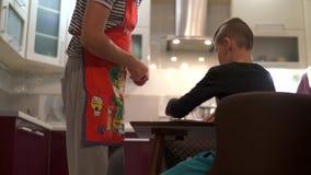 Der Junge schlägt durch die Seiten eines Buches mit kulinarischen Rezepten leicht Er findet das Gericht, das sie kochen Ein Vater stock video