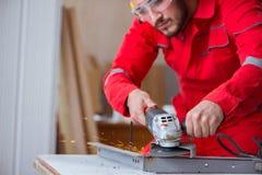 Der junge Schlosser, der mit einer Schleifscheibe arbeitet Lizenzfreie Stockbilder