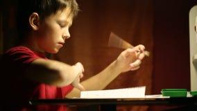 Der Junge am Schreibtisch schreibt in ein Notizbuch stock footage