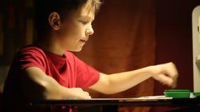 Der Junge am Schreibtisch schreibt in ein Notizbuch stock video