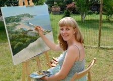Der junge schwangere weibliche Künstler schreibt eine Landschaft und sitzt an einem Gestell Stockfoto