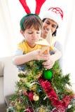 Der Junge setzte einen Stern auf die Oberseite eines Weihnachtsbaums stockbild