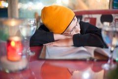 Der Junge setzte seinen Kopf in seine Hände in einem Café ein, das auf einen Auftrag wartet stockfotografie