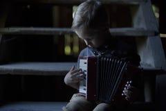 Der Junge sitzt auf der alten hölzernen Treppe und spielt das Akkordeon lizenzfreie stockbilder