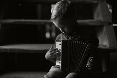 Der Junge sitzt auf der alten hölzernen Treppe und spielt das Akkordeon lizenzfreies stockbild