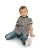 Der Junge sitzt auf dem Boden Stockfotos