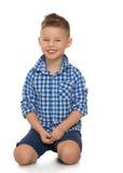 Der Junge sitzt auf dem Boden Lizenzfreies Stockbild