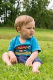 Der Junge sitzt auf dem Gras und dem Spielen Lizenzfreie Stockbilder