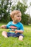 Der Junge sitzt auf dem Gras und dem Spielen Stockbild
