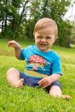 Der Junge sitzt auf dem Gras und dem Spielen Lizenzfreies Stockfoto