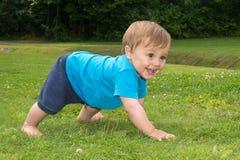 Der Junge sitzt auf dem Gras und dem Spielen Stockfotografie