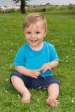 Der Junge sitzt auf dem Gras und dem Spielen Lizenzfreie Stockfotografie