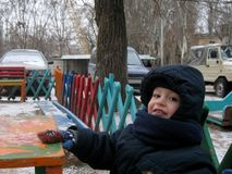 Der Junge sitzt auf dem Spielplatz während eines Winterwegs Lizenzfreie Stockbilder