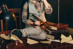 der Junge sitzt auf dem Tisch nahe den selbst gemachten Flugzeugen hergestellt vom Papier und alte Bücher, Vergrößerungsglas und  Lizenzfreie Stockfotos