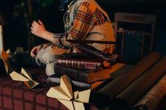 der Junge sitzt auf dem Tisch nahe den selbst gemachten Flugzeugen hergestellt vom Papier und alte Bücher, Vergrößerungsglas und  Lizenzfreies Stockbild