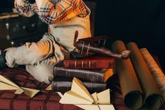 der Junge sitzt auf dem Tisch nahe den selbst gemachten Flugzeugen hergestellt vom Papier und alte Bücher, Vergrößerungsglas und  Lizenzfreies Stockfoto